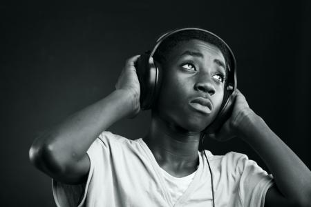 equipo de sonido: Retrato de escuchar música con auriculares adolescente africano.