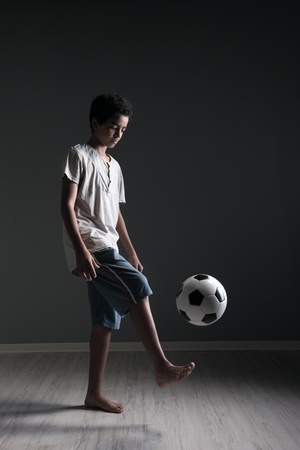 Portrait of young boy playing with a soccerball photo