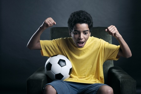 boy ball: Happy young boy waching a soccer match on tv Stock Photo