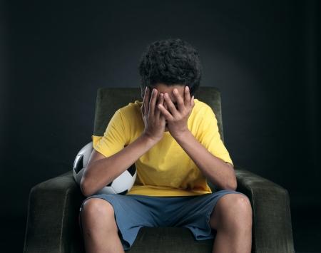 Braziliaanse voetbalfans zittend op een stoel en kijken naar sport op tv. Favoriete team heeft een wedstrijd niet winnen Stockfoto