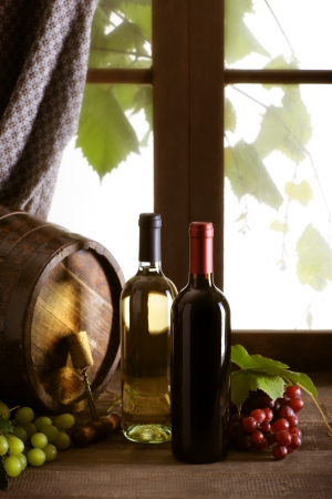 Wine bottles with grapes and barrel on old wooden table photo