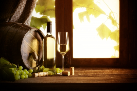 Wine bottle and wineglass on wooden table, photo