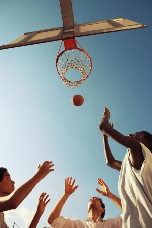 teens playing: Two Afro-American boy and a man playing basketball against blue sky Stock Photo