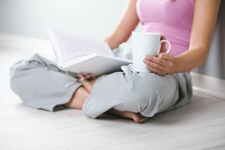 Close up of young woman with book and a cup of coffee sitting on floor photo