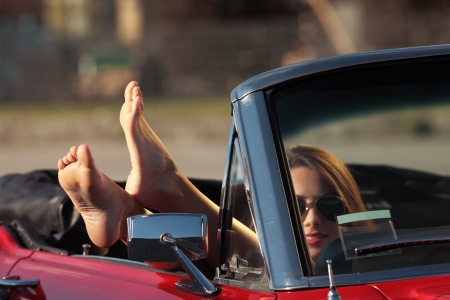Smiling woman with legs out off convertible car window photo
