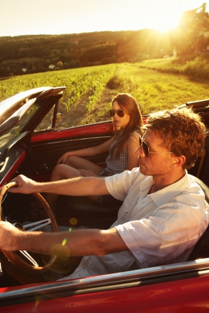 Couple driving vintage convertible car at sunset Stock Photo - 21888598