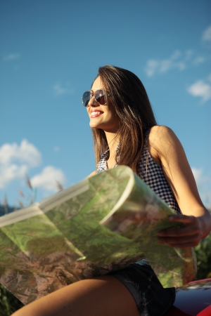 Young beautiful woman wearing sunglasses holding a roadmap photo