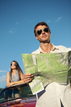 Handsome man holding a roadmap and looking away Stock Photo - 21888607