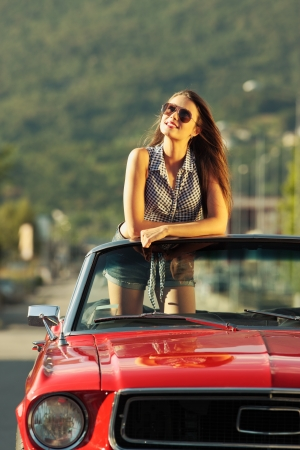 Beautiful young woman in a convertible car enjoying a summer day photo