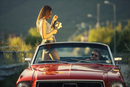old fashioned car: Young beautiful woman filming his boyfriend in a convertible car