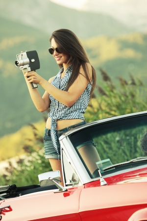 Fashion model with a vintage movie camera in a convertible car Stock Photo - 21888612