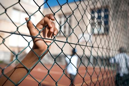 cancha de basquetbol: La mano de un niño se aferra a una cerca, cancha de baloncesto en el fondo