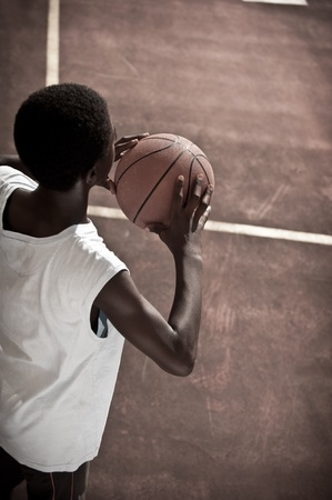 Afro-American boy playing basketball photo