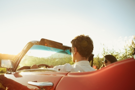 Couple driving convertible car enjoying a summer day at sunset