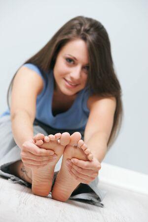 piedi nudi di bambine: Ritratto di una ragazza sorridente facendo esercizio di stretching sul pavimento