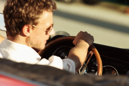 Handsome man driving a convertible car, focus on hand