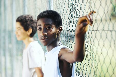 youth culture: Young African boys  leaning up against a chain link fence