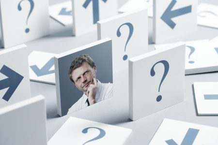 deciding: Portrait of a thoughtful businessman surrounded by question marks and arrows