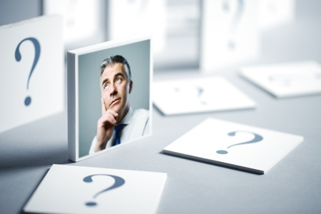 Portrait of a confused businessman surrounded by question marks photo