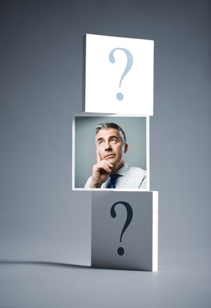 questioning: Portrait of a confused businessman surrounded by question marks