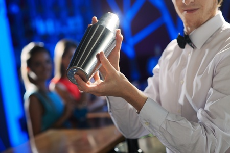 social event: Bartender shaking a cocktail, young women on the background