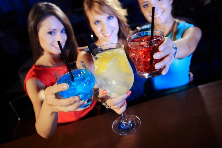 Group of happy beautiful young female friends celebrating in a nightclub with glasses of cocktail in their hands photo
