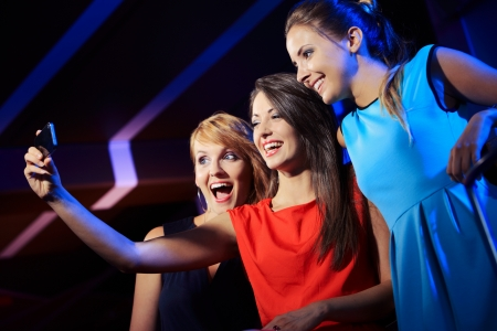 Friends in nightclub taking self-portrait with smartphone photo