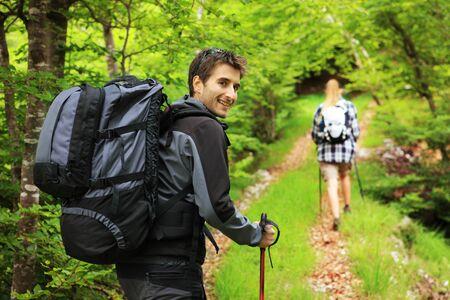 Young couple enjoying a nordic walk, man looking at camera and smiling photo