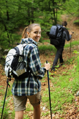 Young couple enjoying nordic walking in a forest, woman looking at camera photo