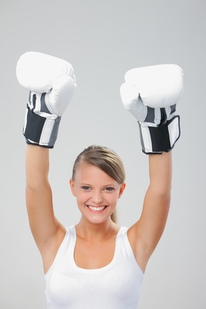 Cheerful girl wearing boxing gloves photo