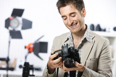 studio photography: Portrait of happy photographer with professional digital camera Stock Photo