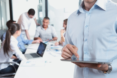 group of workers: Close up of a business man holding his digital tablet, meeting on background