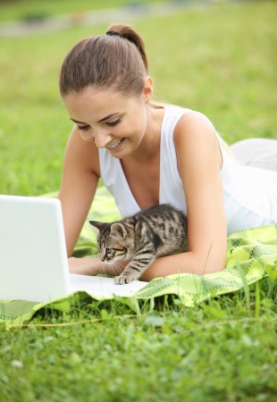 Beautiful girl with her kitty and laptop outdoors photo
