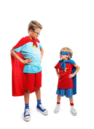 arms akimbo: Portrait of a team of two young heroes Stock Photo