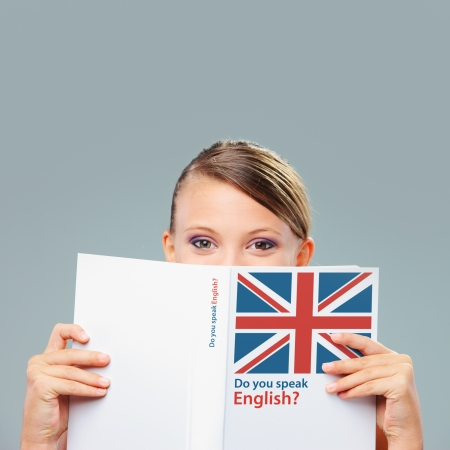 English female student hiding herself behind a book photo