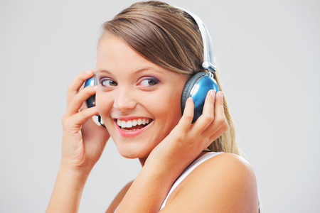 Pretty young woman listening to music on her headphones photo