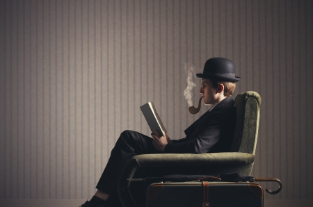 Bizarre man sitting on armchair reading a book and smoking a fake pipe