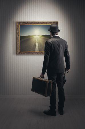 Eleganter Mann mit Vintage-Koffer auf der Suche nach einer neuen Straße