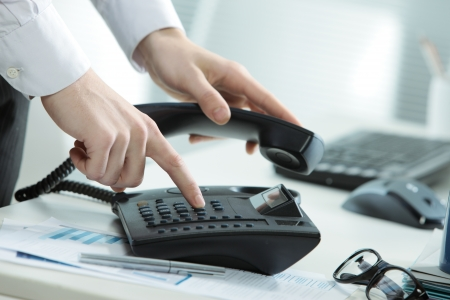 Cropped image of a telephone on a desk with a hand taking the receiver off hook Stock Photo