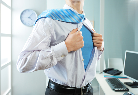 Superhero businessman pulls open shirt in his office photo