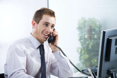 answering phone: A cheerful businessman talking on phone in his office Stock Photo