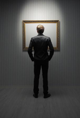 young man standing: Un giovane uomo in piedi davanti a una cornice vuota in un museo Archivio Fotografico