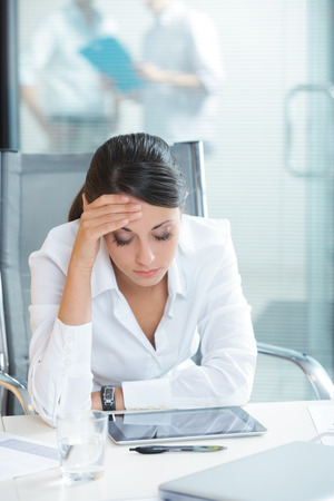 tired worker: Young tired business woman with headache sitting  in workplace