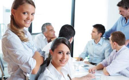 conversa: Retrato de dos j�venes mujeres de negocios de pie mientras habla a su equipo en el fondo