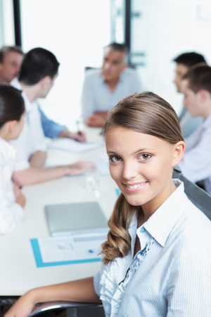 Portrait of a pretty young executive with her team in the background Stock Photo - 22427988