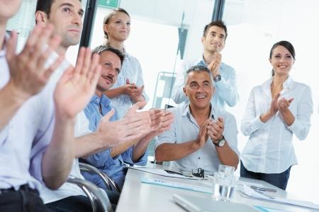 sinergia: Un grupo de gente de negocios feliz aplaudiendo en una reunión