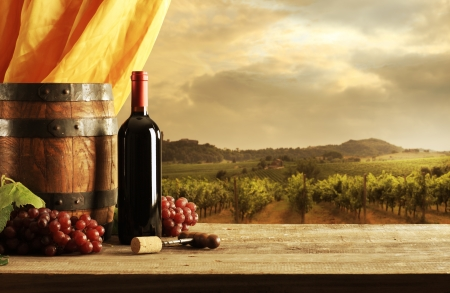 Red wine bottle, barrel and vineyard in sunset photo