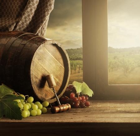 Wijnvat en druiven met wijngaard op zonsondergang Stockfoto
