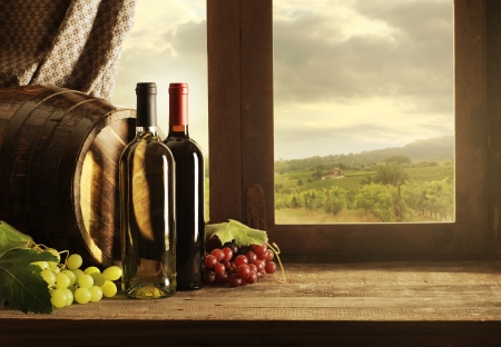 wine and food: Wine bottles, barrels and vineyard in sunset Stock Photo