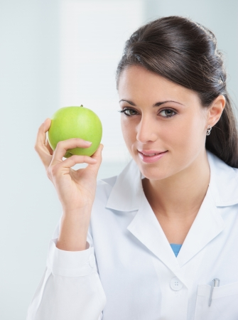 nutritionist: Nutritionist female Doctor holding a green apple